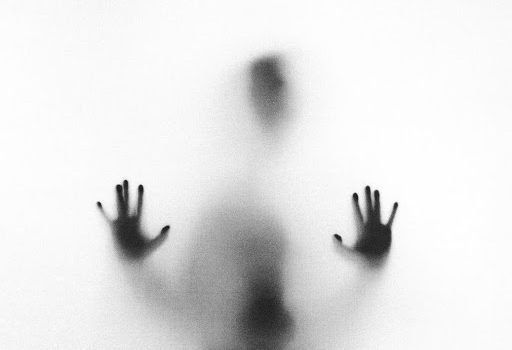 Spooky image of hands on glass